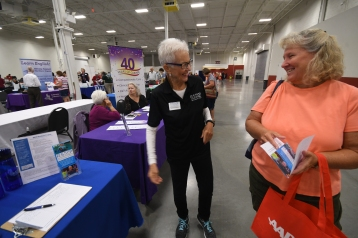 Sue Dussinger (left) talks with an attendee at the Venture into Volunteering Fair in Chantilly in October 2019.
